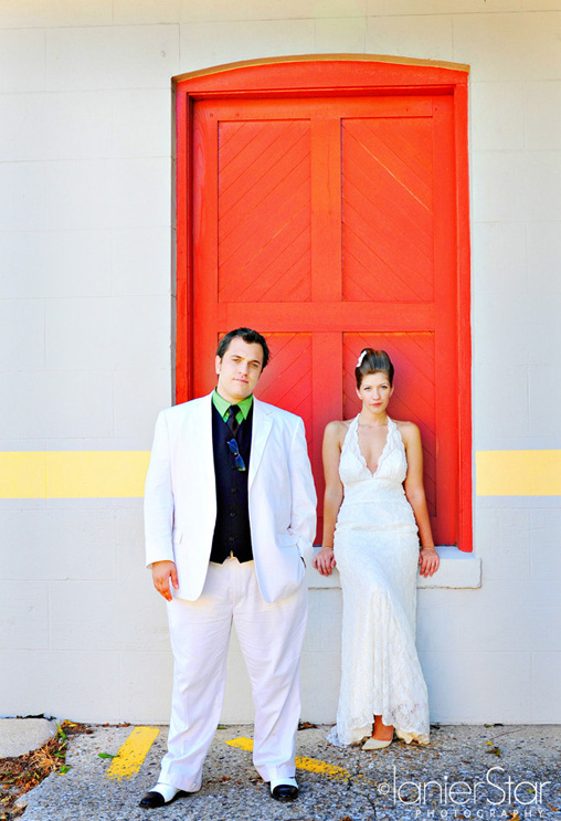 bride and groom in front of red door