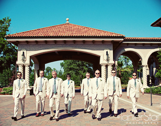 groom and groomsmen walking in front of TPC Clubhouse