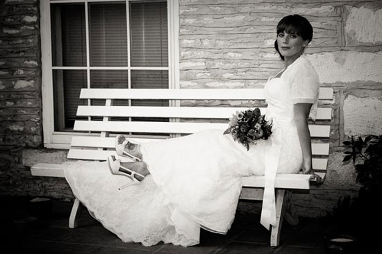 bridal portrait sitting on bench on mansion porch