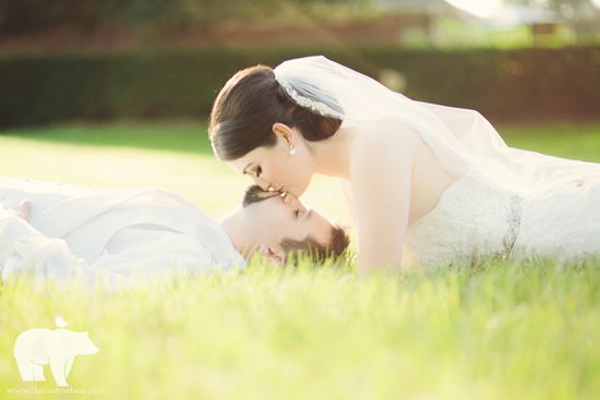 Bride lays on the ground cuddling her groom in the sunshine.