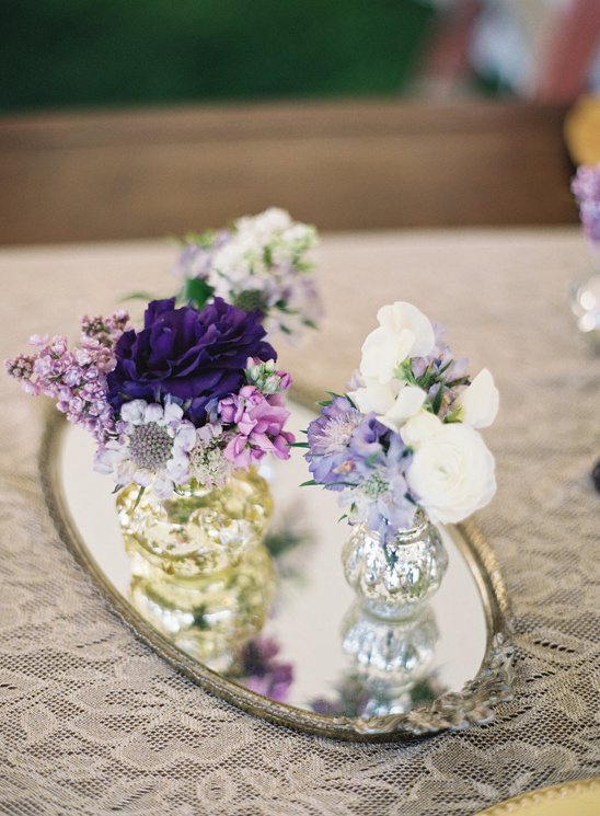 assorted mecury vases placed on a tray with purple florals