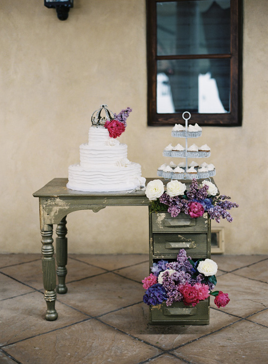 put a cake on a desk open the drawers and put florals in it