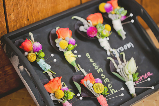 colorful boutonnieres wrapped in yarn and on a chalkboard tray