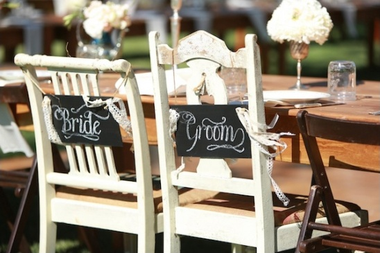 bride and groom signs on chairs