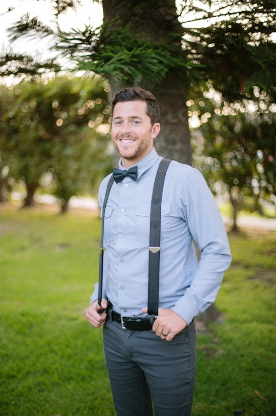 groom in suspenders and bow tie