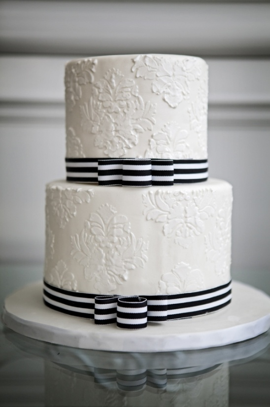 simple white cake with black and white ribbon