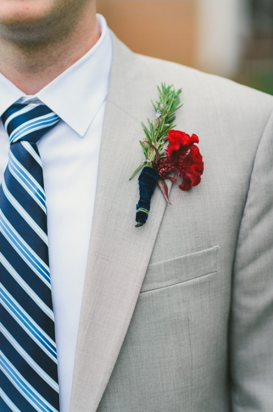 gray suit with blue striped tie and red boutonniere