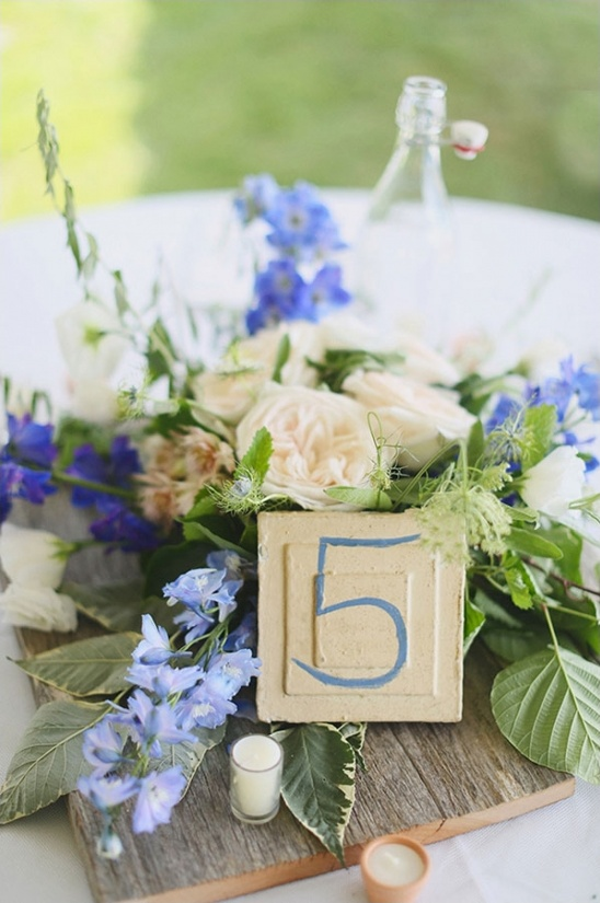 blue and white driftwood themed centerpiece and table number
