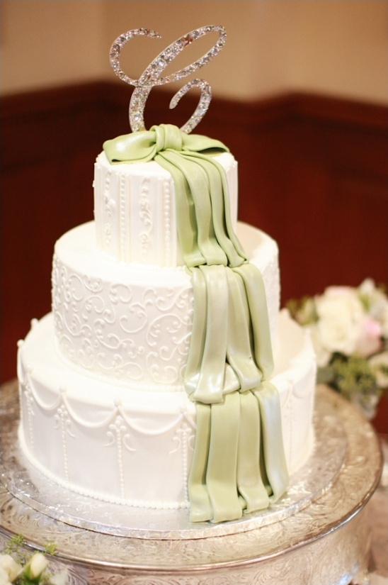 white and green wedding cake with glittery cake topper