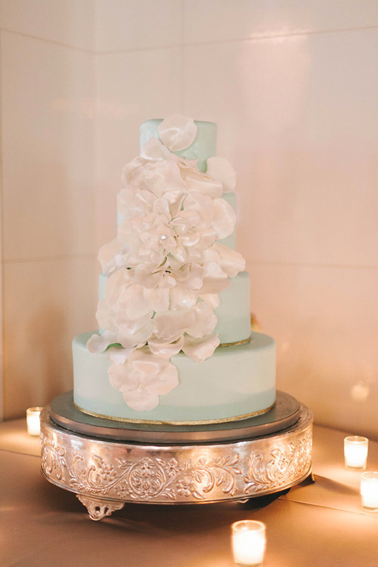 mint and gold wedding cake decorated with white petals