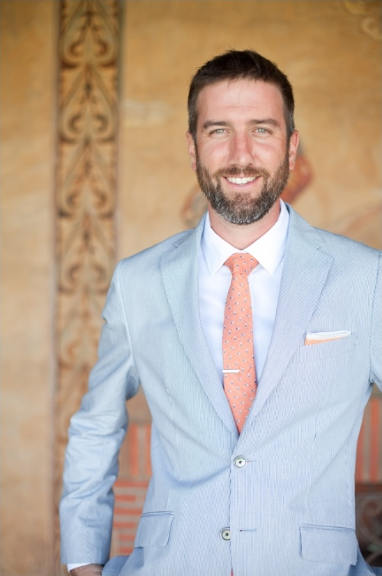 groom in pinstried suit and coral tie