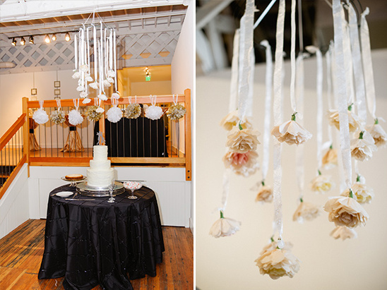 hanging paper flower decoration over cake table