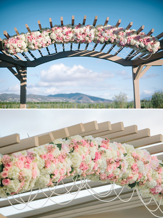 pink and white floral and pearl draped wedding arch