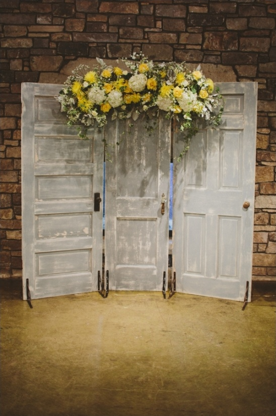 doors with yellow floral arrangement as a ceremony backdrop