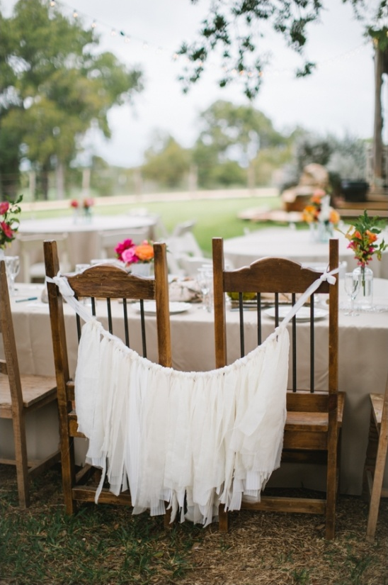 bride and groom seats tied together with a fabric banner