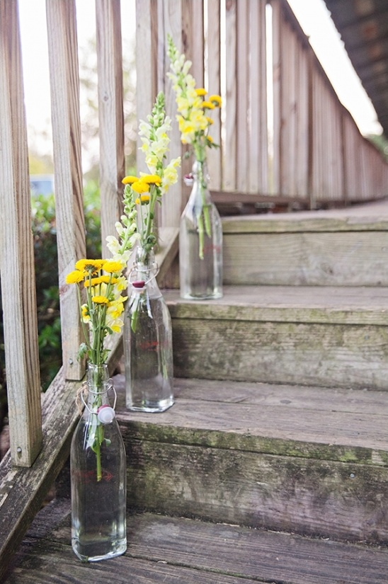 wildflowers in glass bottles brighten up a staircase