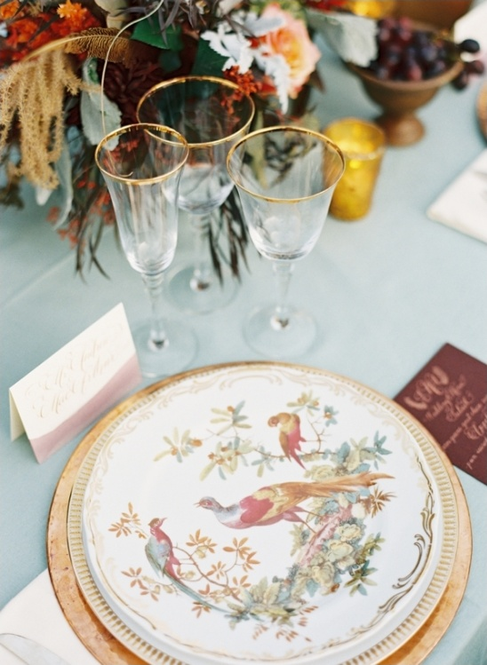 gold rimmed glasses and pheasant patterned plates