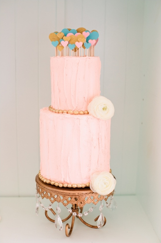 pink tiered cake with heart toppers