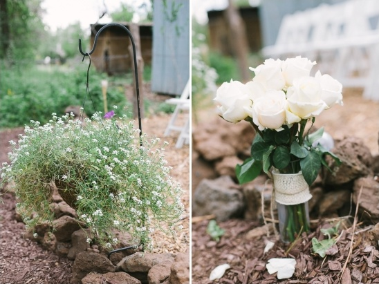hanging potted plants and white roses lined the aisle