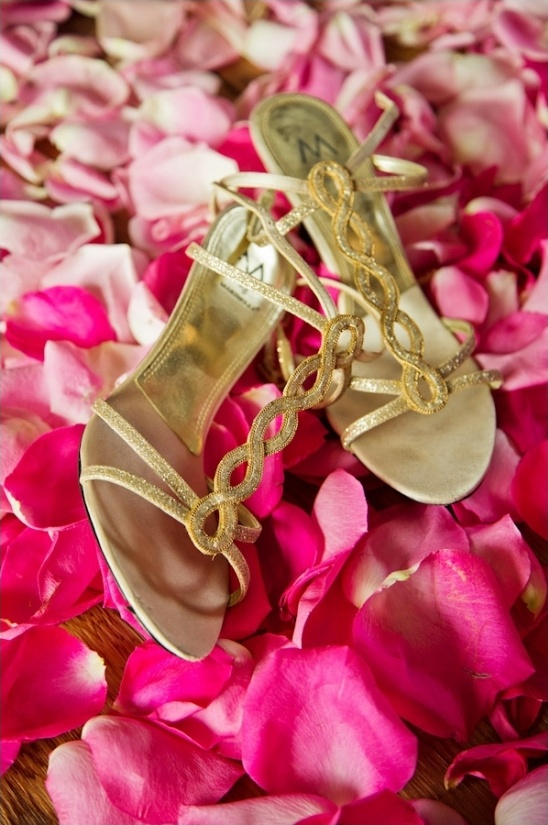 gold wedding shoes on a bed of pink rose petals