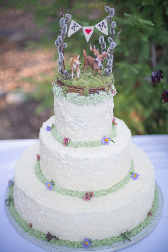 forest wedding cake with mini bunting and deer topper