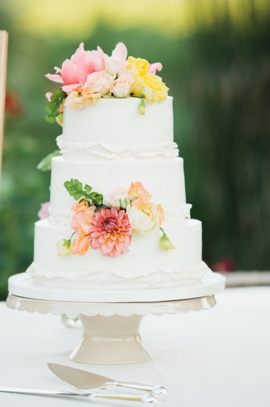 white wedding cake with bright floral accents