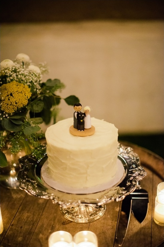 simple white wedding cake with cute custom topper