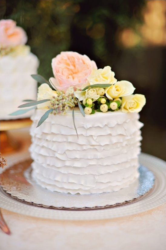ruffled white wedding cake with floral topper