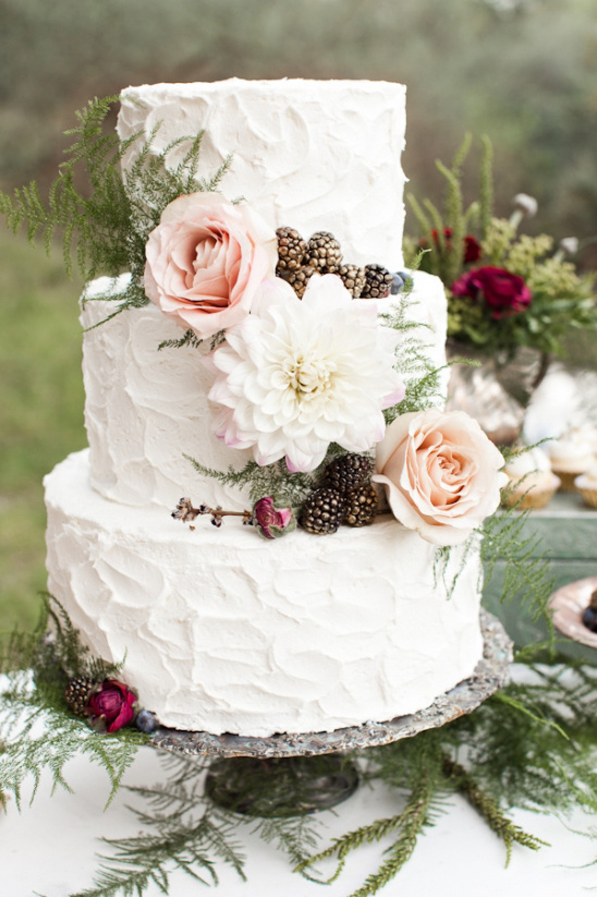 white wedding cake with gold dusted berries