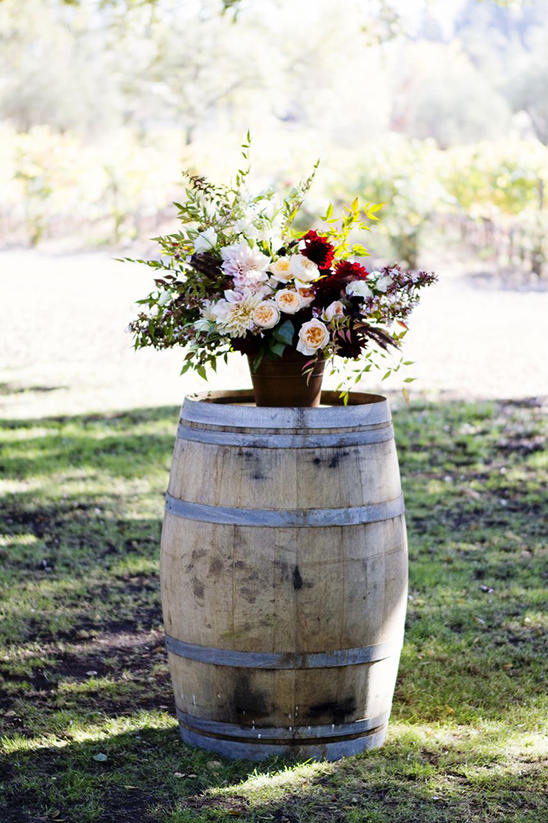 wine barrels and floral pieces used for ceremony backdrop