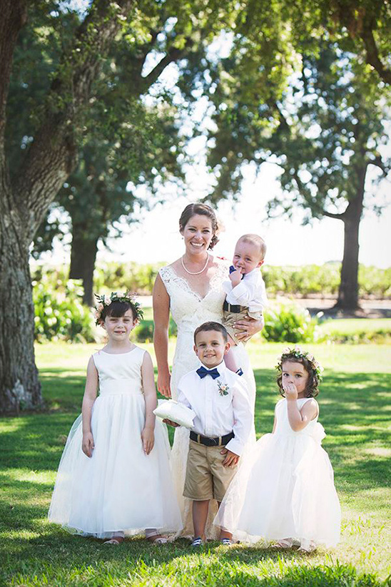 happy bride with the flower girls and ring bearers