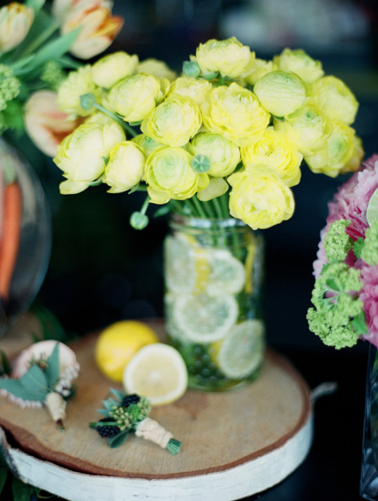 yellow ranunculus with lemon slices in glass vase