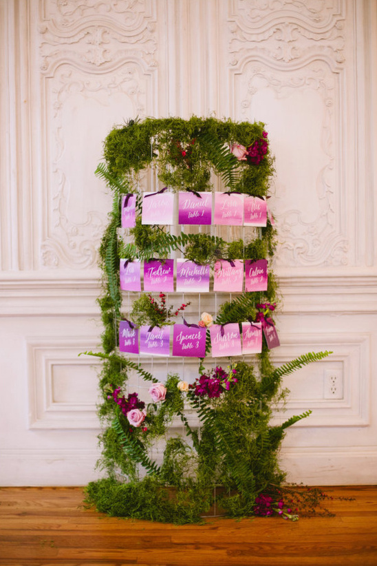 purple dip dyed escort cards on moss covered stand