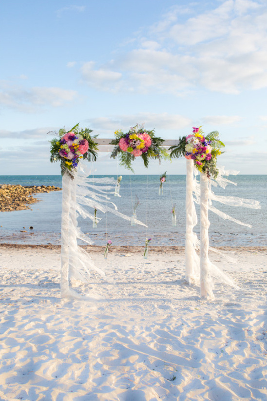 floral and ribbon wrapped wedding arch