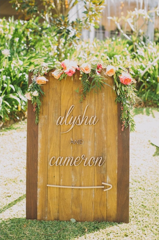 wooden wedding sign drapped in roses