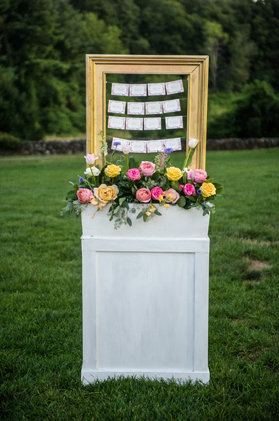 framed hanging escort cards with floral piece