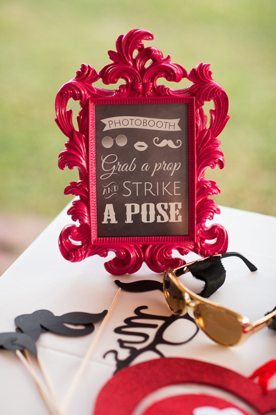 grab a prop and strike a pose photobooth sign