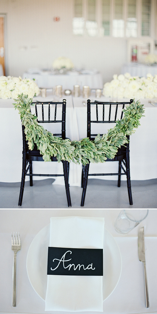 sweetheart seats drapped with greenery garland and chalkboard place cards