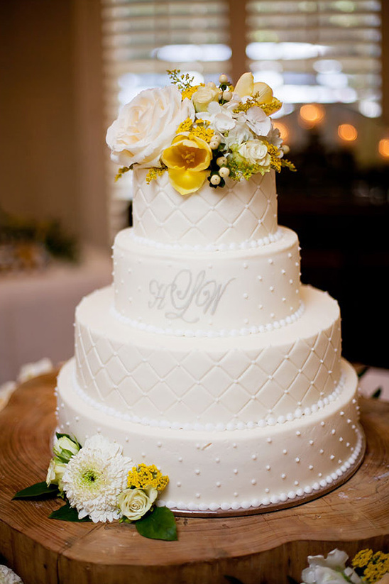 white wedding cake with yellow accent florals