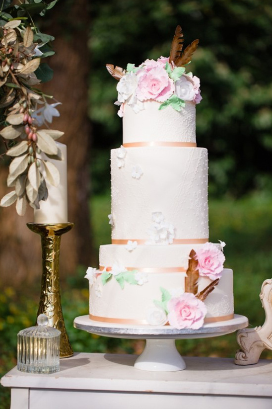 pastel wedding cake with florals and feathers