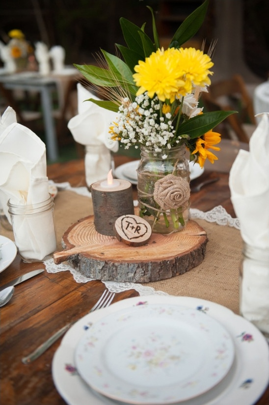 raw wood centerpieces with mason jar floral arrangement