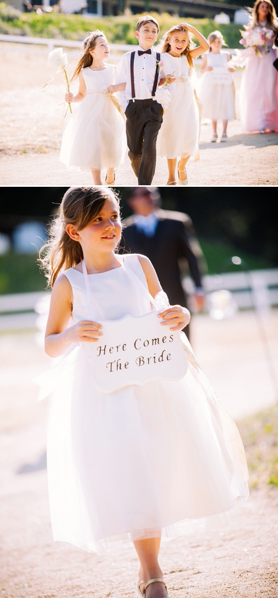 cute ring bearer with two flower girls and here comes the bride sign