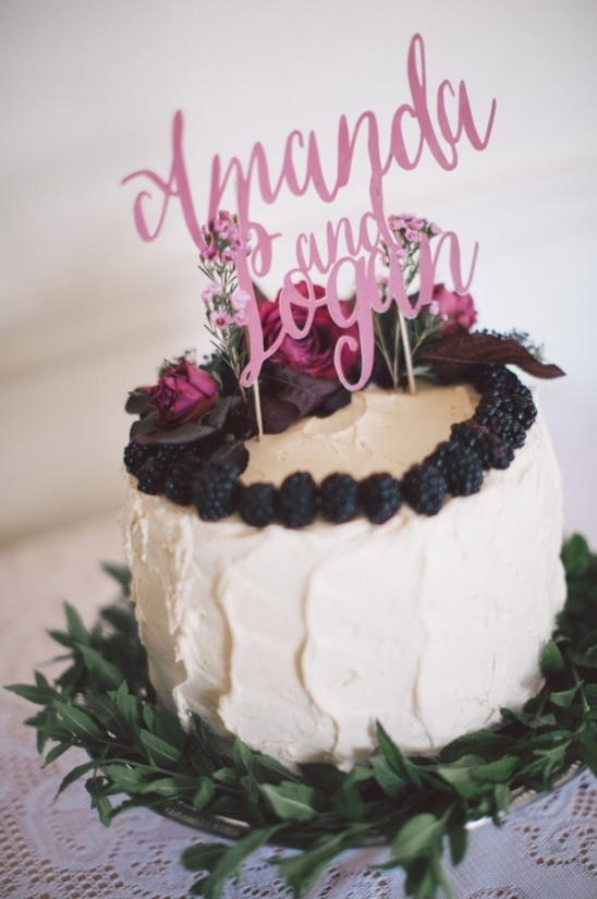 berry and floral topped cake with name cake topper