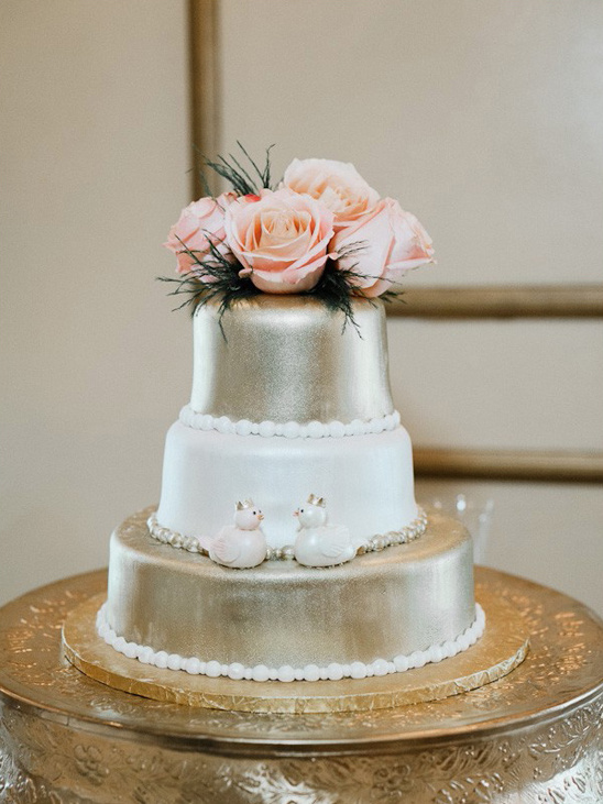 gold and white rose topped wedding cake