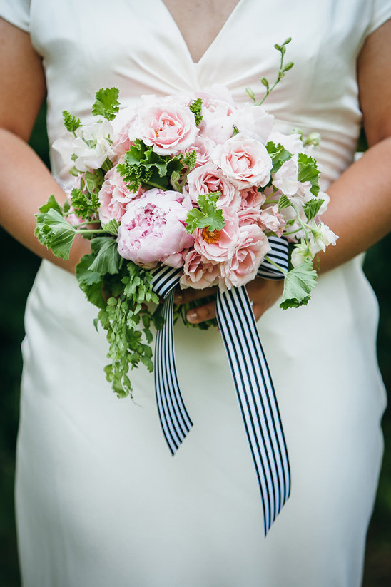 pink bouquet tied up with a black and white ribbon