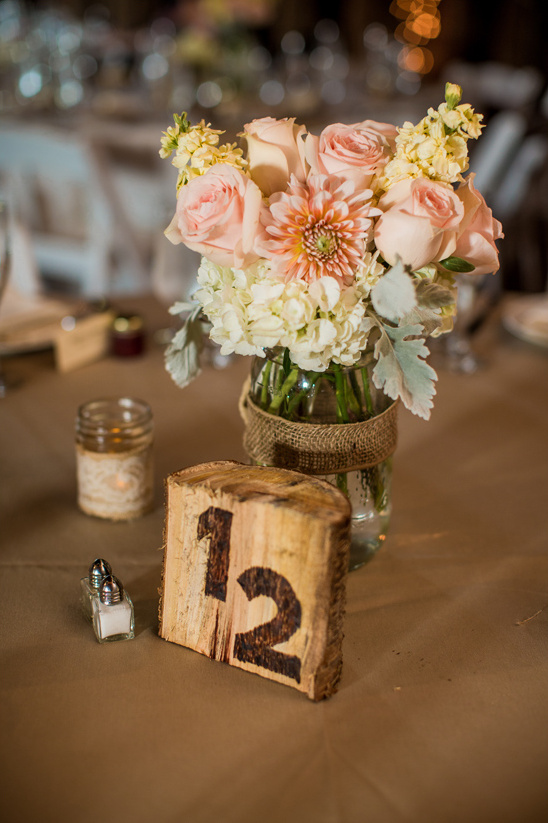 raw wood table number and peach centerpiece