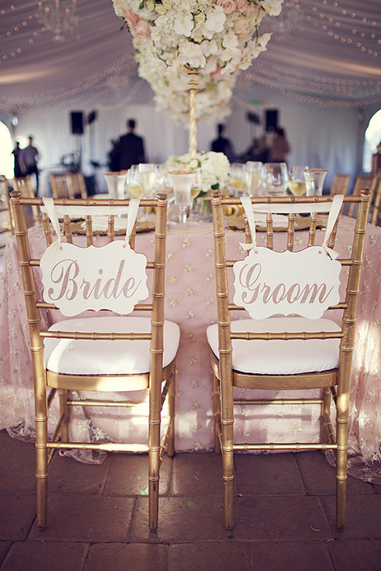 bride and groom signs on gold chairs