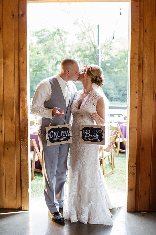 bride and groom holding chalkboard signs