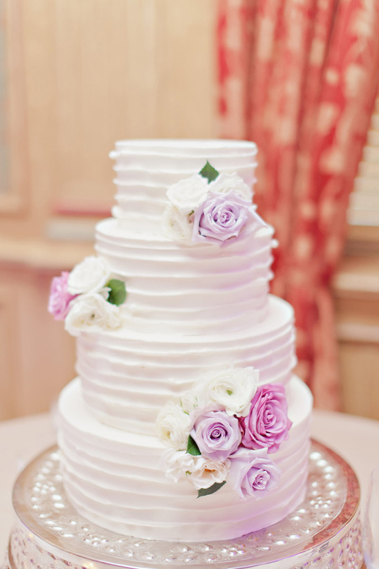 white ruffle cake with purple flower accents