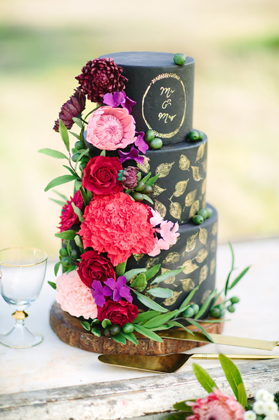 black and gold cake with floral cascade